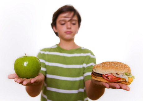 an image of a child holding a burger and an apple