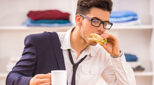 image of a man eating breakfast on the go