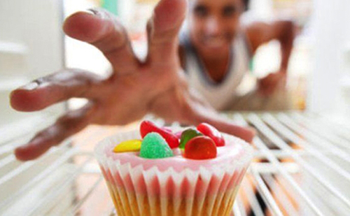 image of a lady reaching for a cup cake