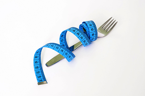 image of a fork with a measuring tape around it
